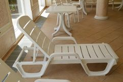 White plastic beach chair is inside the luxurious swimming pool Royalty Free Stock Images