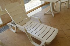 White plastic beach chair is inside the luxurious swimming pool Stock Photo
