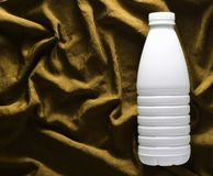 White plastic bottle of yogurt on yellow silk tablecloth, top view stock photography