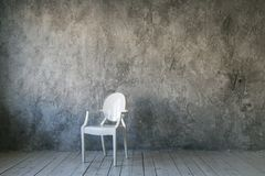 White plastic chair on concrete wall background. Loft room. Wooden floor. daylight. Free space for text. royalty free stock photography