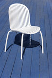 White plastic chair over a blue wooden floor. Outdoor Royalty Free Stock Photo