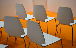 White plastic chairs over orange floor in a conference room Royalty Free Stock Image