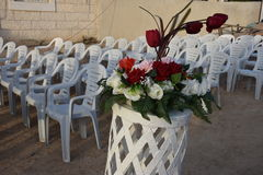 White plastic chairs in a row and a bouquet of roses for a wedding Royalty Free Stock Images