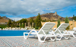 White plastic chaise lounges on the bank of pool. Rest on a resort. White plastic chaise lounges on the bank of pool royalty free stock image
