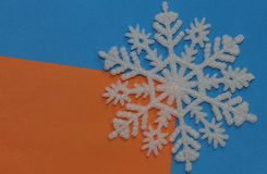 White plastic Christmas cold snowflake, decor element lies on the background of two-color orange blue stock image