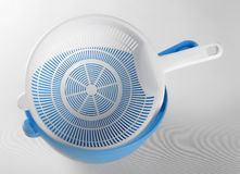 White plastic colander in blue bowl Royalty Free Stock Images