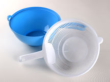 White plastic colander to blue bowl Stock Photography