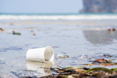 White plastic cup on the beach. White abandoned plastic cup on the beach. Pollution stock photo