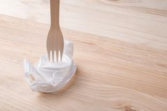 A white plastic cup crushed by a wooden eco fork. The concept of non-plastic utensils royalty free stock photography