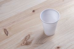 White plastic Cup stands on a wooden table of natural color. The concept of abandonment of plastic utensils stock photography