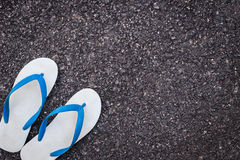 White plastic flip flop shoe on black asphalt road Stock Image