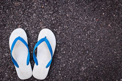 White plastic flip flop shoe on black asphalt road Stock Photos