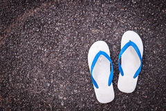 White plastic flip flop shoe on black asphalt road Stock Image