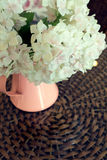 White plastic flowers in pink flower vase on the rattan weave Royalty Free Stock Photo