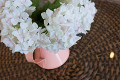 White plastic flowers in pink flower vase on the rattan weave Stock Images
