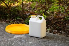 White plastic gallon of oil for color combinations on the cement floor.  Stock Image
