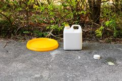 White plastic gallon of oil for color combinations on the cement floor.  Stock Photos
