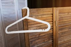 White plastic hanger without clothes, on the background of an empty brown wooden screen and wardrobe royalty free stock images