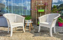 White plastic lounge chairs with a small wooden table and garden decorations in the backyard at home stock photo