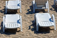 White plastic loungers are standing on the sand of the beach. A row of white plastic loungers standing on the sand of the beach stock photo