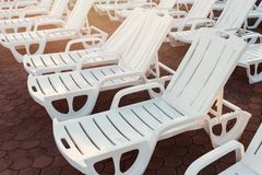 White plastic loungers on stone brick pavers on beach at sunset. Sunset, relax, vacation, holidays. Concept stock image