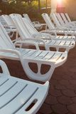 White plastic loungers on stone brick pavers on beach at sunset. Sunset, relax, vacation. Holidays concept royalty free stock photos