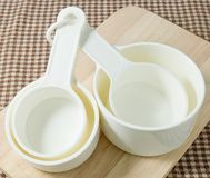 White Plastic Measuring Cups on Wooden Board Stock Photo
