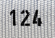 White plastic mesh with black number 124 Royalty Free Stock Image