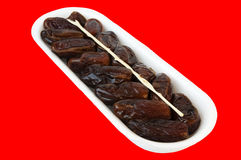 White plastic plate with delicious dates Royalty Free Stock Photo