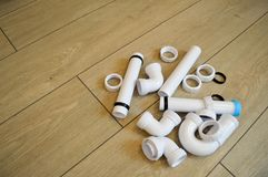 White plastic plumbing, plumbing pipes, smooth and curved, fittings, flanges, rubber gaskets Royalty Free Stock Photos