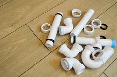 White plastic plumbing, plumbing pipes, smooth and curved, fittings, flanges, rubber gaskets Stock Images
