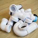White plastic plumbing, plumbing pipes, smooth and curved, fittings, flanges, rubber gaskets Stock Photos