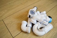 White plastic plumbing, plumbing pipes, smooth and curved, fittings, flanges, rubber gaskets. Stock Image