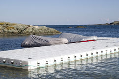 White plastic pontoon for boats and two covered boats Stock Images