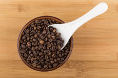 White plastic spoon in brown ceramic bowl with coffee beans Stock Photo