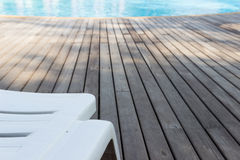 White plastic sunbed beside swimming pool Royalty Free Stock Images