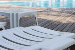 White plastic sunbed beside swimming pool Stock Image