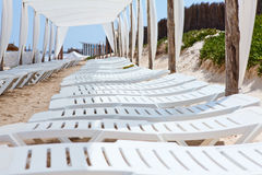 White plastic sunbeds on sandy beach Royalty Free Stock Photography