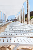 White plastic sunbeds in sandy beach Stock Photography