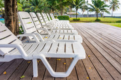 White plastic sunbeds on wooden deck in garden Royalty Free Stock Image