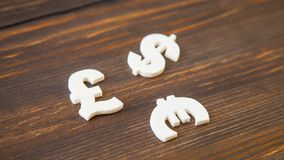 White plastic symbols of different currencies. On wooden background Stock Photography