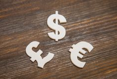 White plastic symbols of different currencies. On wooden background Royalty Free Stock Photo