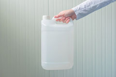 White plastic tank canister in female hand. White unlabeled plastic 5 liters tank canister in female hand, chemistry and chemical liquids mock-up container Stock Image