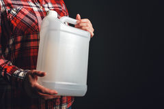 White plastic tank canister in female hand. White unlabeled plastic 5 liters tank canister in female hand, chemistry and chemical liquids mock-up container stock images