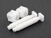 White plastic toilet bolts and nuts on a dark background. Royalty Free Stock Images
