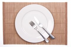 White plate on a bamboo mat Stock Photos