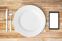 White plate, blank smartphone screen, fork and knife on wooden t. Able, mock up vector illustration