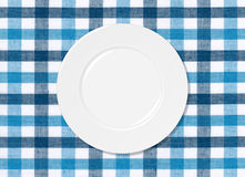 White plate on blue and white tablecloth Stock Photo