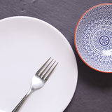White plate and bowl. White plate and moroccan bowl on a slate background Royalty Free Stock Photos