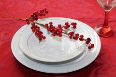 Red and white holiday table place setting. White plate and bowl with red berries, red tablecloth and red stemmed wine glass Royalty Free Stock Photos